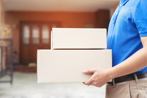 L'uomo di consegna pacchi indossa guanti protettivi blu, protegge i germi di igiene e i batteri di un pacco attraverso un servizio inviato a casa. mano che tiene la consegna e la presentazione del cliente che accetta una scatola.