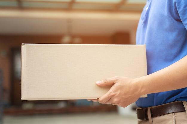 L'uomo di consegna pacchi indossa guanti protettivi blu, protegge i germi di igiene e batteri di un pacco attraverso un servizio inviato a casa