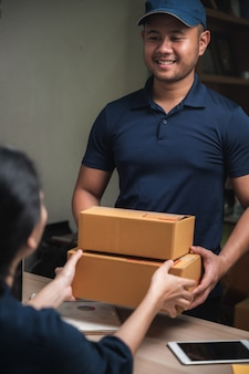 Servizio di consegna pacchi per lavoro da casa, donna che riceve pacchi da uomo delle consegne
