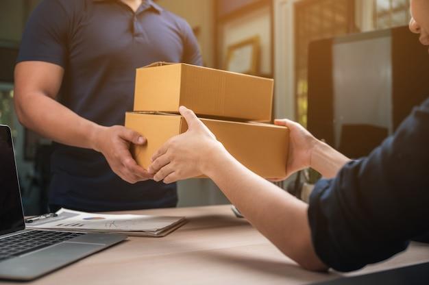 Consegna pacchi con buona profondità di campo. lavoratore amichevole con servizio di consegna di alta qualità.