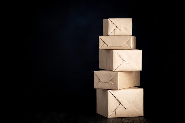Pacchi o regali avvolti in carta da imballaggio su sfondo nero