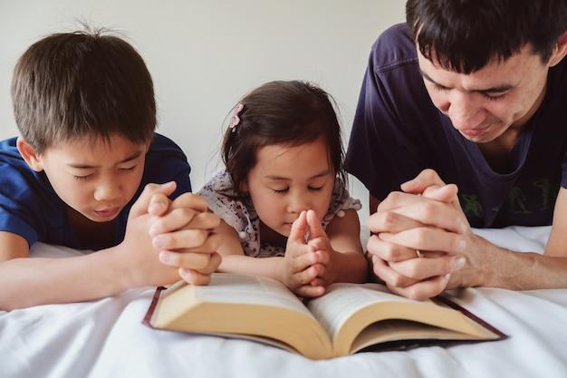 Genitore e figli che pregano sul letto, la famiglia prega insieme