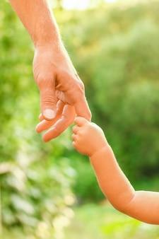 Il genitore che tiene la mano del bambino con uno sfondo felice