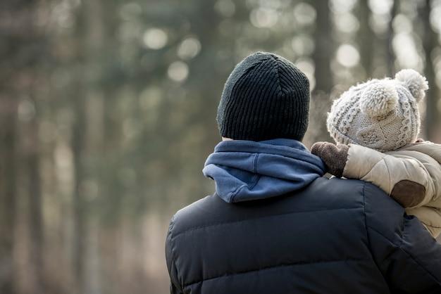 Genitore in possesso di un bambino in un caldo abbigliamento di lana in una giornata invernale rivolto verso una foresta nebbiosa, copia laterale dello spazio.