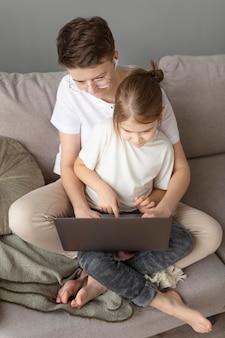Genitore e bambino sul divano digitando