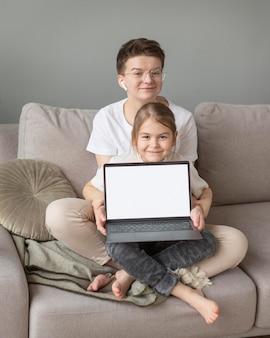 Genitore e bambino sul divano con laptop full shot