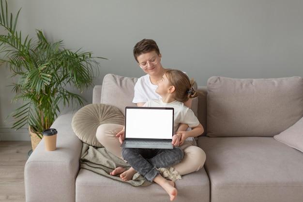 Genitore e bambino sul divano con il computer portatile