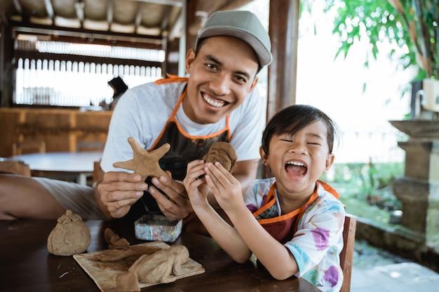 Genitore e figlio che producono merci con argilla
