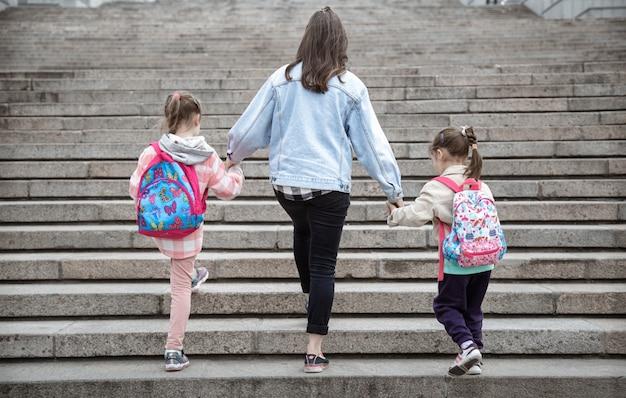 Genitore e allievo della scuola primaria vanno di pari passo. mamma di due ragazze con uno zaino dietro la schiena. inizio delle lezioni. primo giorno d'autunno.