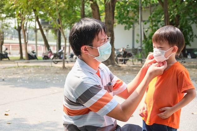 Genitore che mette maschera sul suo bambino asiatico del ragazzo del bambino, papà e figlio che indossano maschera medica protettiva nell'area pubblica