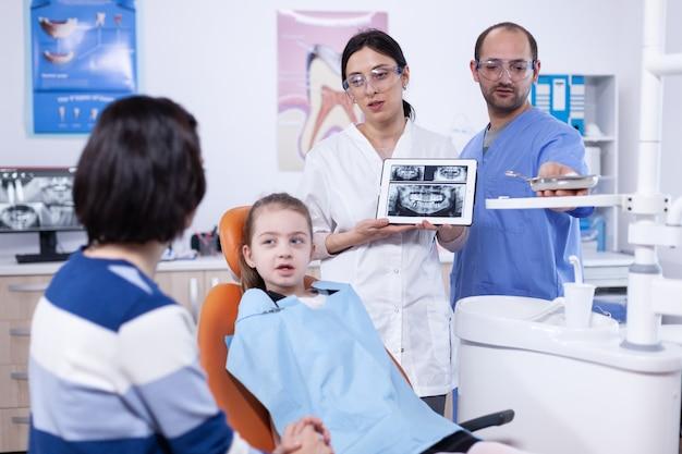 Genitore con la bambina in studio dentistico che ascolta il dentista del medico che parla del trattamento della cavità. stomatologo che spiega la diagnosi dei denti alla madre del bambino in clinica sanitaria che tiene i raggi x.