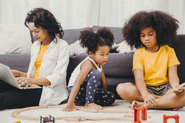 I genitori lavorano a casa da internet computer laptop effetto della malattia pandemica del virus covid-19 madre sana vita felice di stare e giocare con i suoi figli