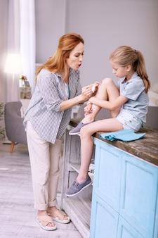 Amore dei genitori. piacevole donna premurosa che si prende cura di sua figlia mentre soffia sulla sua ferita