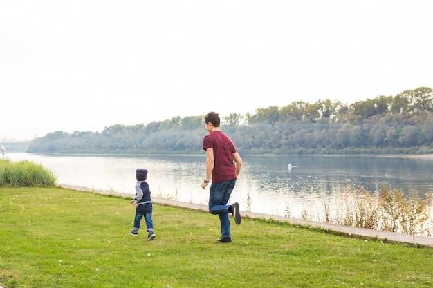 Concetto di genitorialità e figli. padre che gioca con un figlio piccolo, cercando di prenderlo