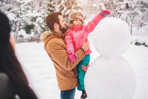 Concetto di genitorialità, moda, stagione e persone - famiglia felice con bambino in abiti invernali all'aperto.