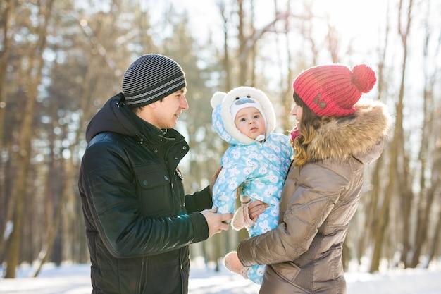 Concetto di genitorialità, moda, stagione e persone. famiglia felice con bambino in abiti invernali all'aperto.