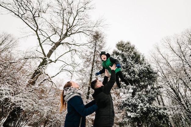 Concetto di genitorialità, moda, stagione e persone - famiglia felice con bambino in abiti invernali che cammina all'aperto nel parco. il concetto di celebrare un buon natale.