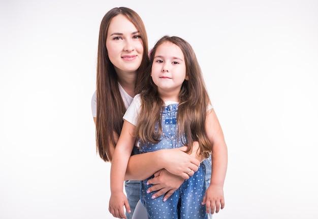 Concetto di genitorialità, famiglia e bambini - un ritratto di una madre e la sua bambina si divertono e sorridono sulla superficie bianca