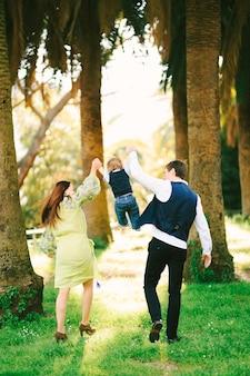 I genitori si divertono con il loro bambino sotto le palme in una giornata di sole.