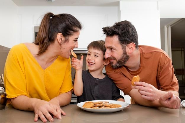 Genitori e ragazzo che mangiano i biscotti Foto Premium