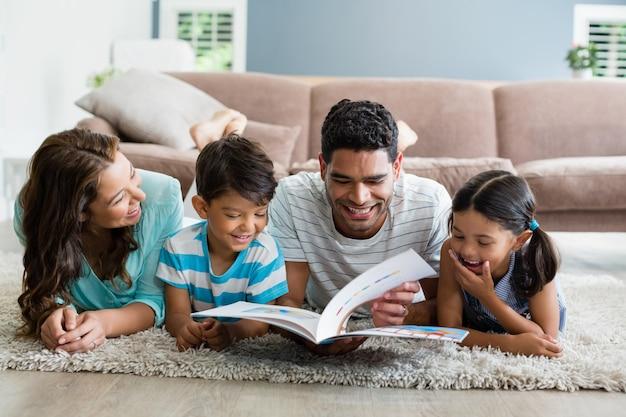 Genitori e bambini che si trovano sul tappeto e libro di lettura in salotto