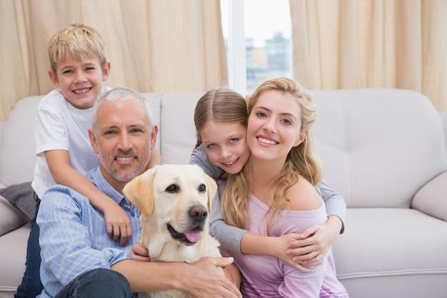 Genitori e bambini sul tappeto con labrador