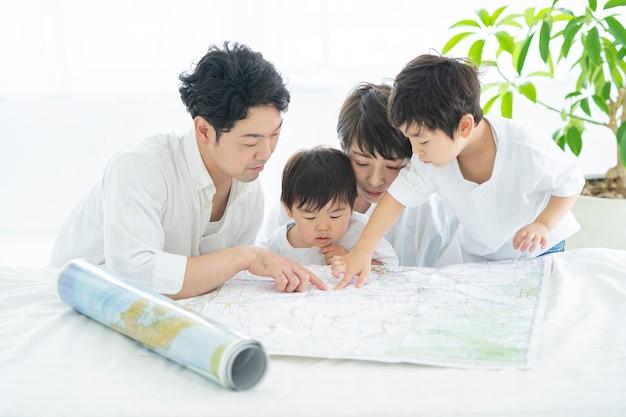 Genitori e bambini che studiano felici usando le mappe ã£âƒâ» genitori e bambini che pianificano viaggi usando le mappe