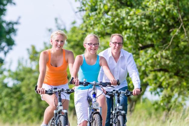 I genitori e la figlia fanno un giro in bicicletta o in bicicletta sulla strada di campagna