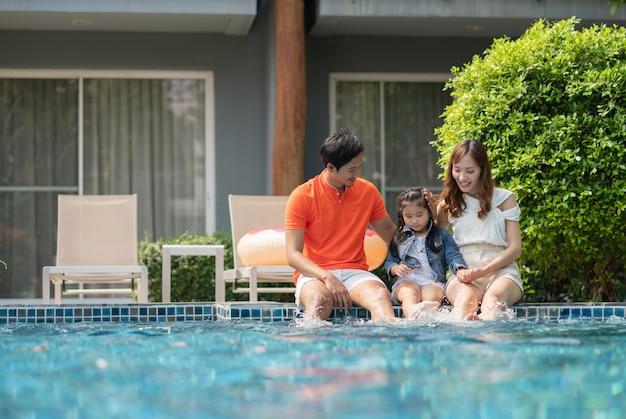 Genitori e figlia usano le gambe per spruzzare acqua sul bordo della piscina mentre si rilassano in hotel in estate.