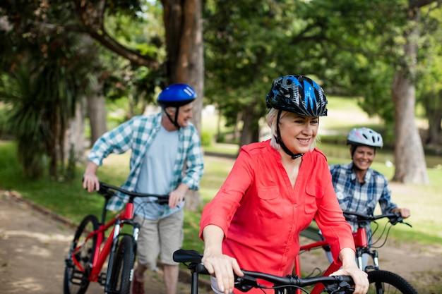 Genitori e figlia che camminano con la bicicletta nel parco