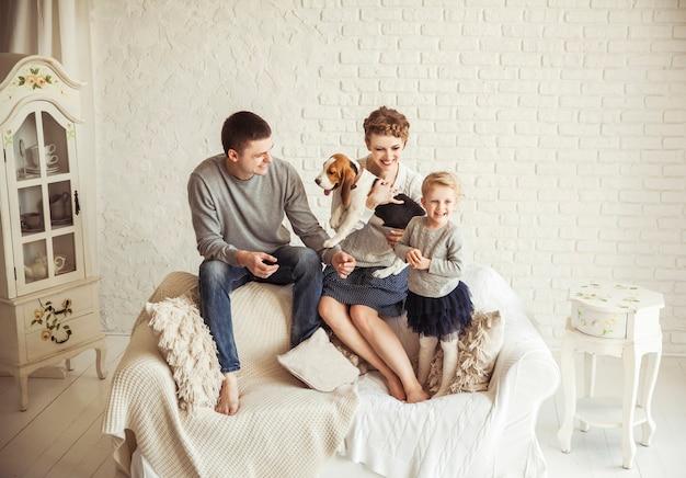 Genitori, figlia di cinque anni con un cane seduto sul divano in soggiorno