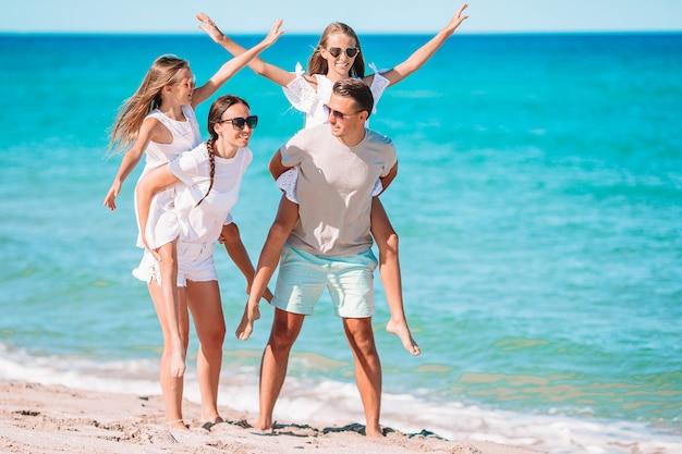 I genitori danno ai bambini cavalcate sulla spiaggia