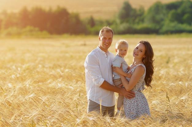 Felicità dei genitori, camminando sul campo con il bambino. madre, padre e bambino svaghi insieme all'aperto. copyspace, luce solare