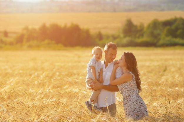 Felicità dei genitori, camminando sul campo con il bambino