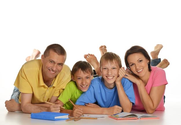 I genitori aiutano i bambini a fare i compiti sul pavimento