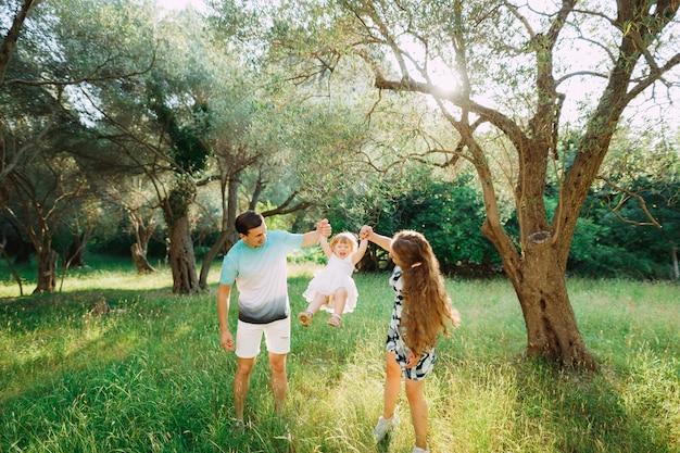 I genitori tengono le mani dei bambini e si lanciano nell'oliveto in montenegro.