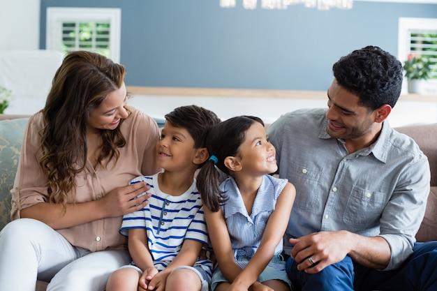 Genitori e bambini che interagiscono sul divano nel soggiorno