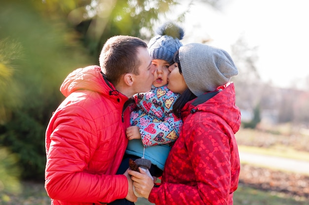 I genitori baciano il bambino in autunno park