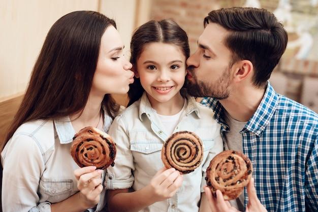 I genitori baciano la ragazza sulla guancia e mangiano i panini.