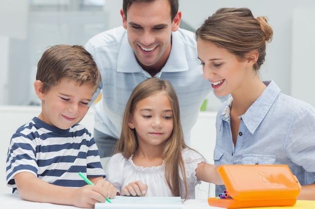 I genitori guardano i loro figli disegnare