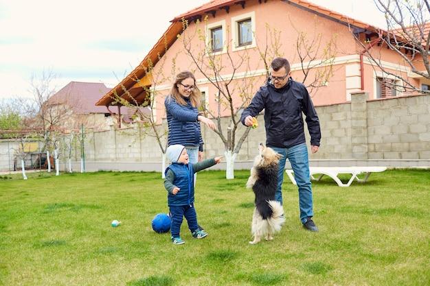 Genitori, madre, padre e figlio giocano nel cortile di casa