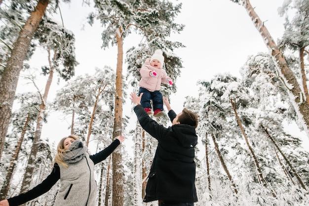 Genitori che giocano con sua figlia nel parco forestale invernale.