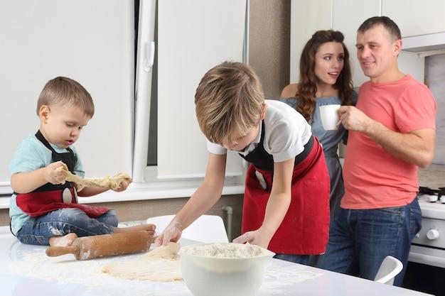 I genitori vedono i loro figli piccoli, che impastano la pasta sul tavolo della cucina