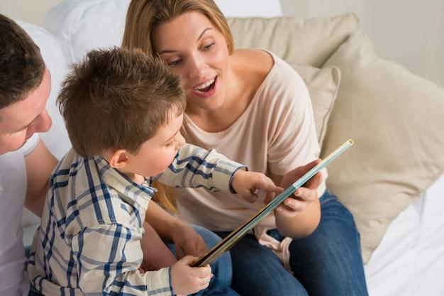 Genitori che si siedono con la storia della lettura del bambino all'interno