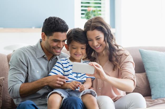 Genitori e figlio che controllano le foto nel telefono cellulare