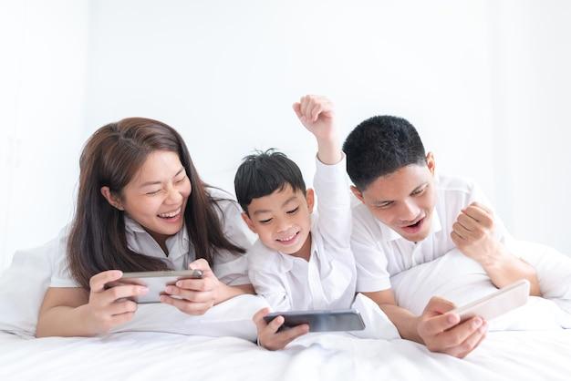 Genitori e figlio che giocano a videogiochi per smartphone a casa