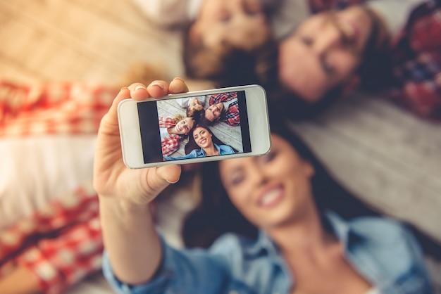 I genitori e i loro figli facendo selfie usando uno smartphone