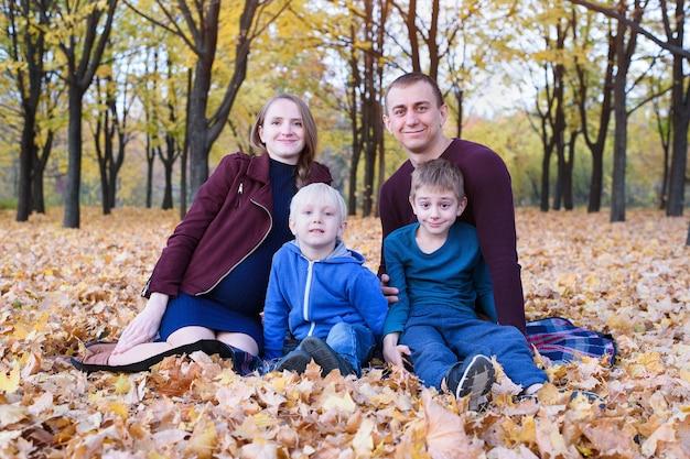 Genitori e due figli si rilassano e chiacchierano nel parco