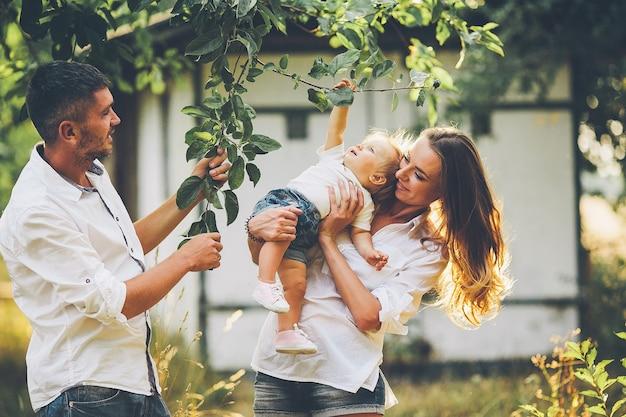 Genitori con bambino che godono di picnic in una fattoria con alberi di mele e ciliegi.