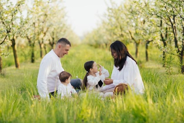 Genitori con bambini che si godono un picnic nel giardino di primavera